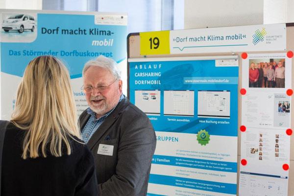 """Franz Pieper stellt das Projekt """"Dorf macht Klima-mobil"""" einer Interessentin vor (Foto: Zukunftsnetz Mobilität NRW)"""