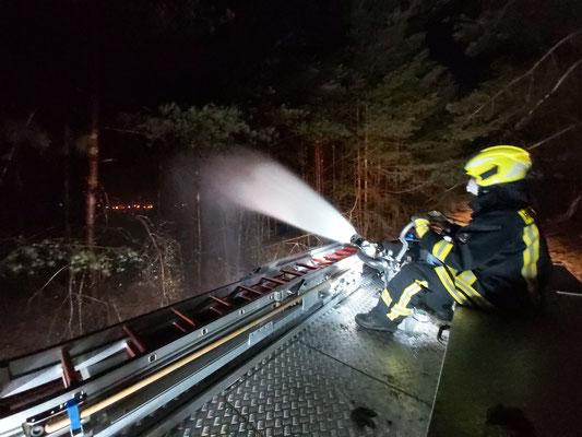 Wässern des Brandriegels in der Nacht um ein Übergreifen des Feuers auf eine neue Fläche zu verhindern.
