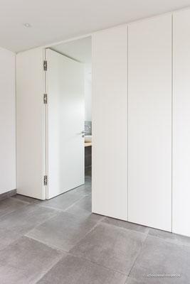 Wandverkleidung mit Zimmertür und integrierten Einbauschränken
