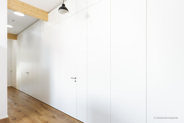Wandverkleidung mit Zimmertüren und integrierten Einbauschränken
