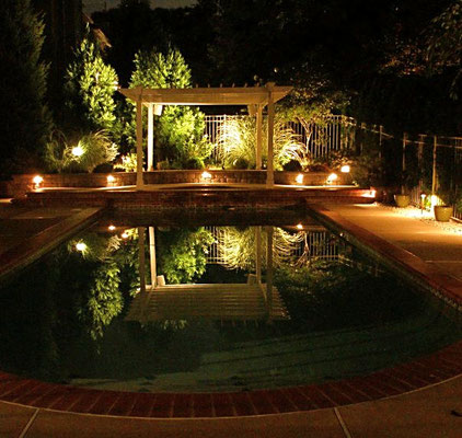 Captivating mirror lighitng technique using pool water to reflect landscape lighting on pergola, Bergen County, NJ