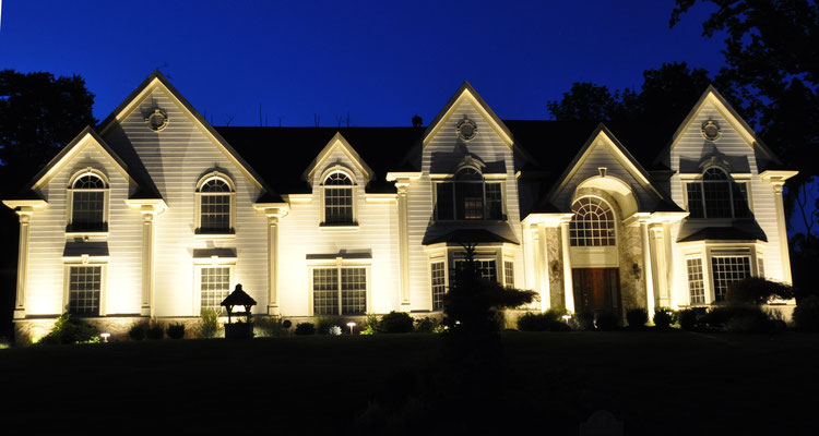 """The distinctive architectural elements of this home's facade are accentuated in the evening with the """"grazing"""" technique. Upper Saddle River, NJ"""