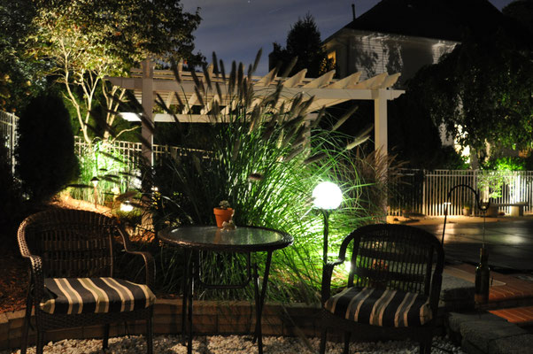 a BBQ downlight along with a low voltage NightOrb in front of tall grass completes a cozy sitting area