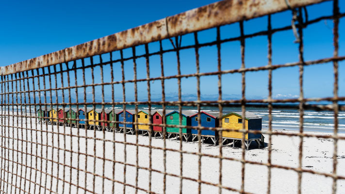 The colourful beach houses of Muizenberg, South Africa, through a fence