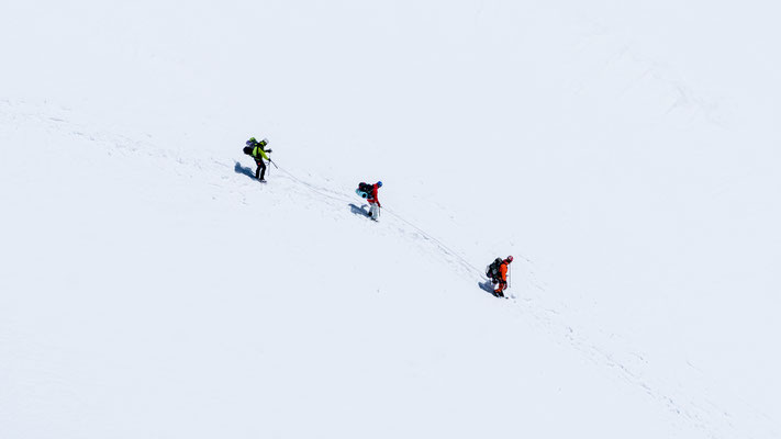 Mountain cyclists going down Mont Blanc through snowfield