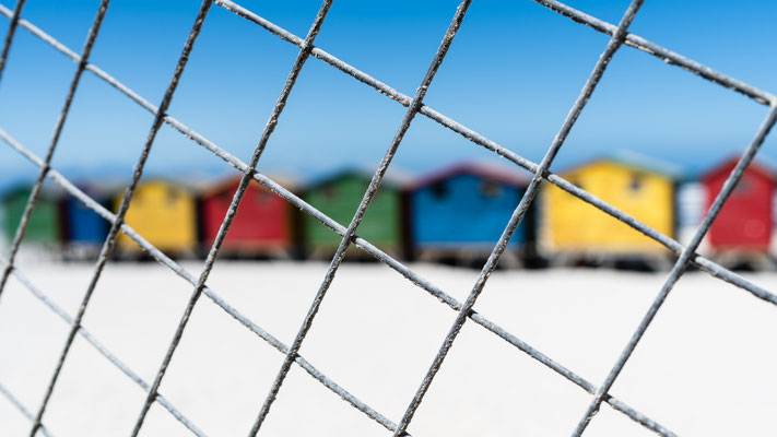 The colourful beach houses of Muizenberg, South Africa, seen through a fence