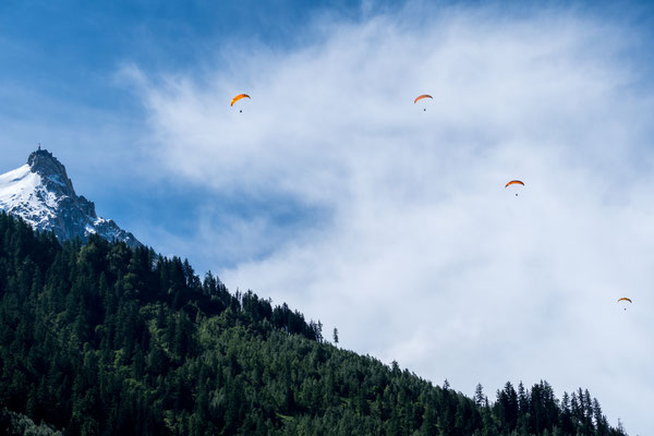 Four paragliders circling at Aiguille du Midi