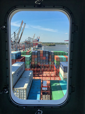 Looking down the bow of a container ship through a cabin window