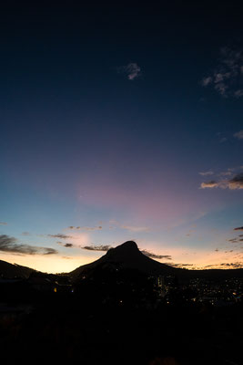 Silhouette of Lion's Head way after sunset with pink sky