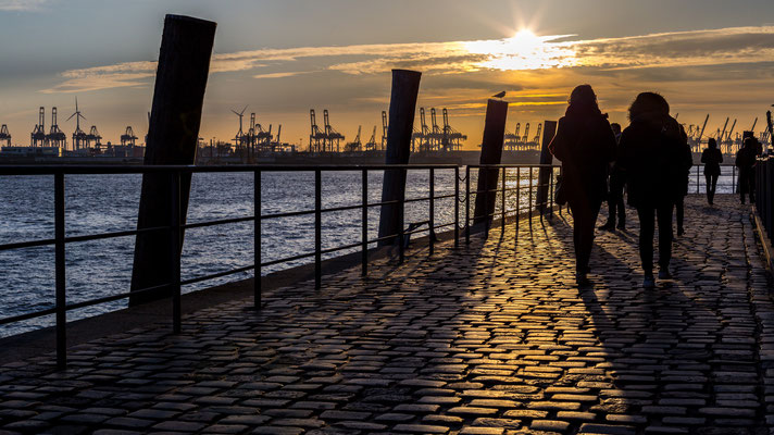 People walking along Hamburg harbour during sunset