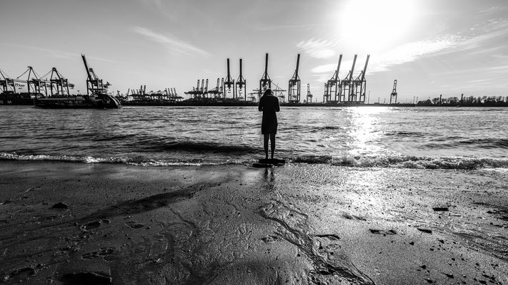 Woman standing barefoot at Elbe river in Hamburg