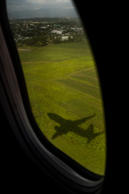 Using the airplane window to frame the shadow of the plane while landing on Fiji