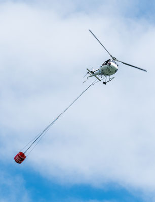 Helicopter carrying a water bucket to extinguish a fire in New Zealand