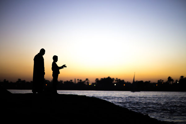 Father and son standing at the river Nile in Luxor, Egypt