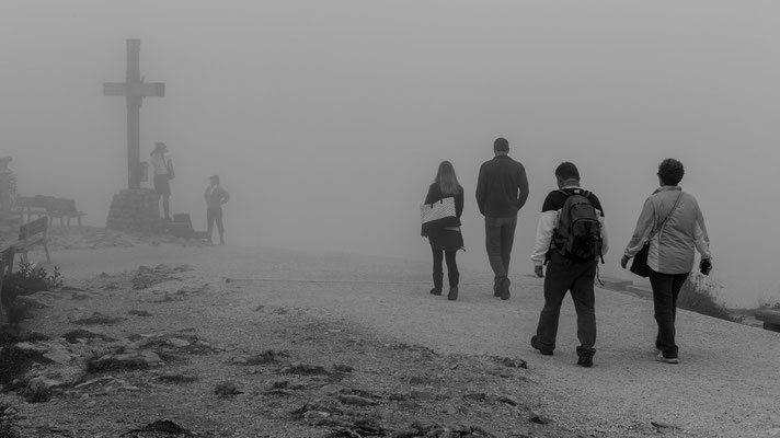 People walking towards a summit cross in the fog in Bavaria