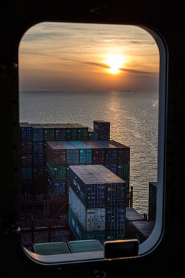 Looking towards sunset and the bow of a container ship through a cabin window