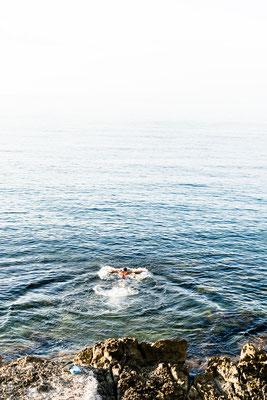Men swimming during sunrise in Fertilia, Sardinia