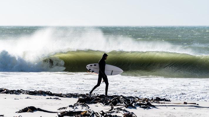 A surfer in a wet suit walking along Kommetjie beach, South Africa