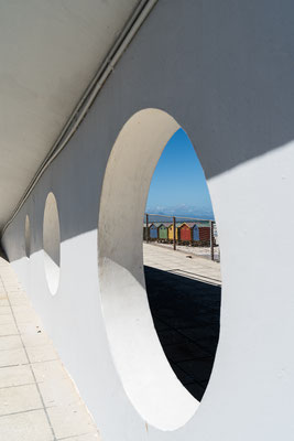 Looking at the colourful beach houses of Muizenberg through a wall hole