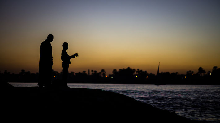 Father and son silhouette after sunset at Nile river