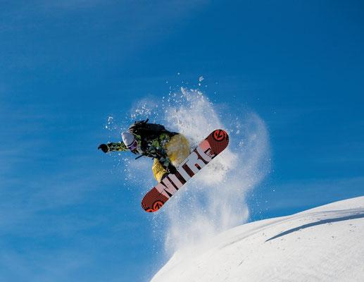 Snowboardker beim Sprung über Geländekante