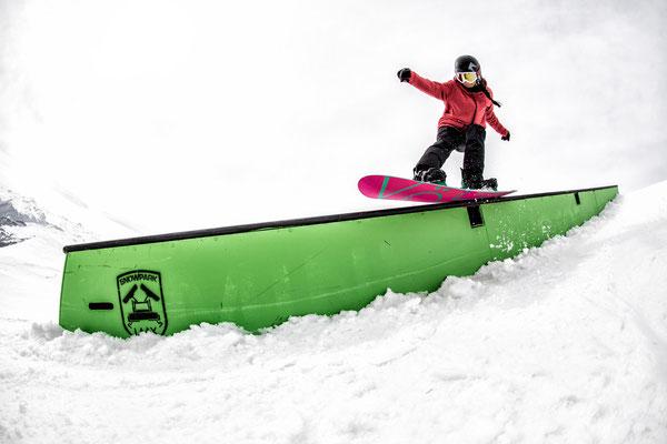 Snowboarder auf dem Rail im Park