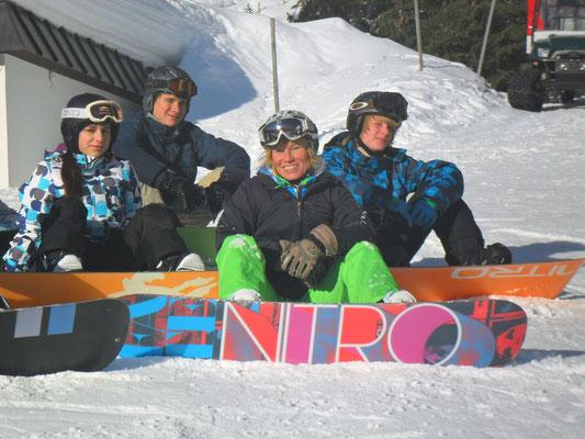 Snowboardkursgruppe bei der Pause am Hang