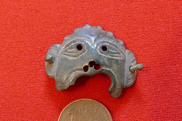 mittelalterlicher Bronzebeschlag in Form eines stark stilisierten Menschenkopfes