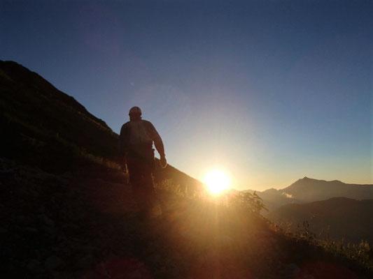 五竜岳山頂から昇る朝日に照らされながら劔岳を目指します。