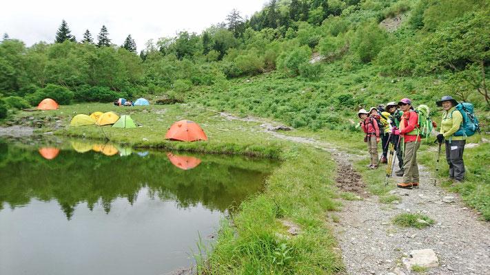 白根御池テント場横を通って登る 御池に映る逆さテント