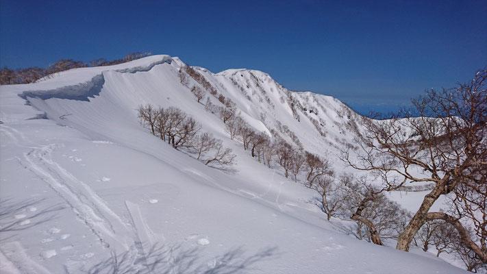 雪庇を抱えた外輪山。真中が三田原山