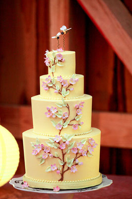 Pastel yellow buttercream tiers with handmade apple blossoms and leaves.