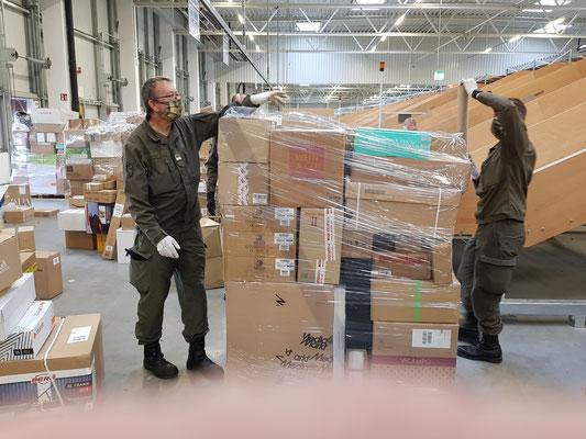 Die Pakete werden von den Rollcontainern auf Paletten geschlichtet