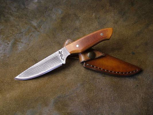 Couteau plate semelle, longueur totale 16cm, lame 8,6cm. Acier 440A. Côtes en micarta canvas marron. Gravure à l'eau-forte. Etui en cuir