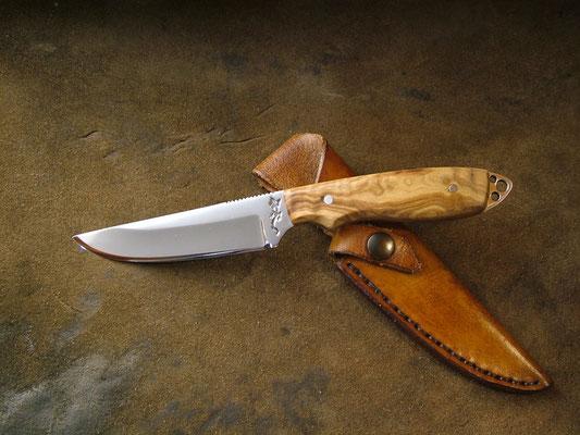 Couteau plate semelle, longueur totale 19cm, lame 9,5cm. Acier 440B. Côtes en bois d'olivier. Etui en cuir
