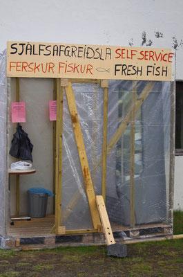 eine Kühltheke, ein Schild mit Waren und Preisen, eine kleine Kasse und fertig ist der unbemannte 24 h Fischladen
