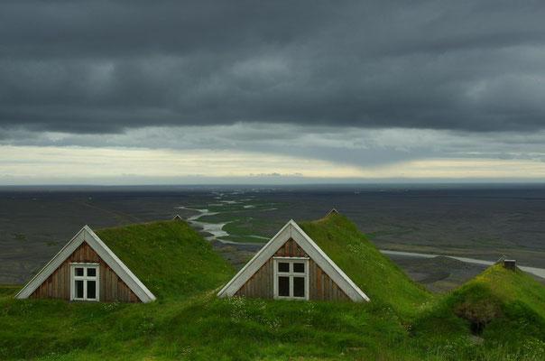 Blick ins Tal hinweg über die Dächer eines kleinen Bergbauernhofes