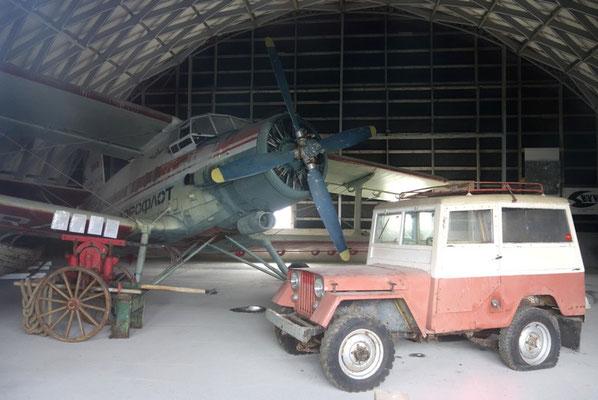 und noch ein altes Flugzeug und Auto in einem Fluzeughangar