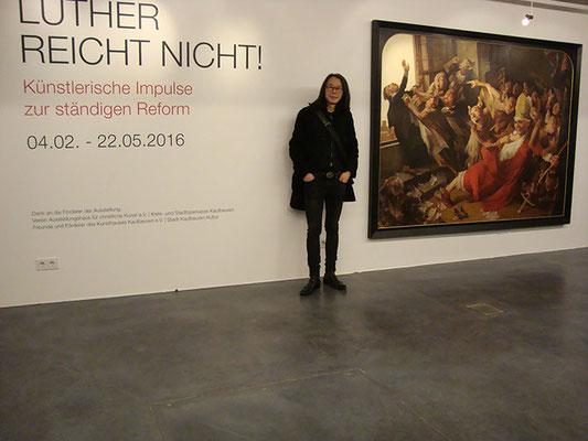 """Yongbo Zhao vor seinem Bild """"Kelch der Päpste II"""", Ausstellung """"Luther reicht nicht!"""", Kunsthalle Kaufbeuren 2016"""
