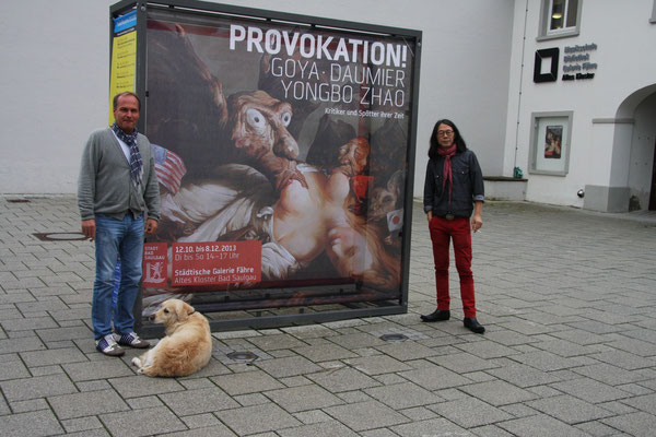 "Yongbo Zhao with a friend and collector in front of the exhibition poster ""Provocation! Goya, Daumier and Yongbo Zhao - Critics and Mockers of their Tmes"" at the Municipal Gallery ""Fähre"" at the Old Cloister Bad Saulgau, 2013"