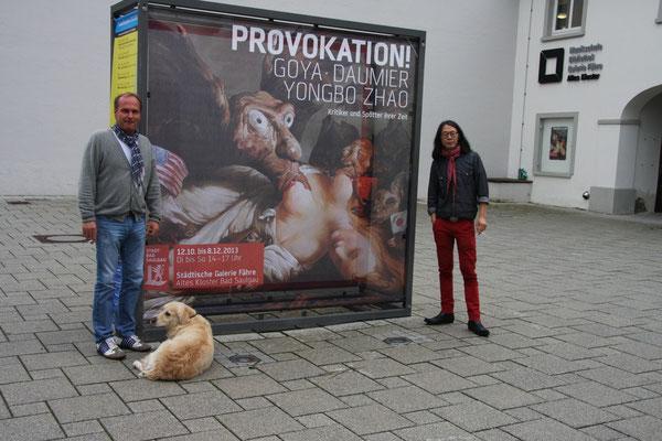"""Yongbo Zhao mit einem Freund und Sammler vor dem Plakat zur Ausstellung """"Provokation! Goya, Daumier und Yongbo Zhao – Kritiker und Spötter ihrer Zeit"""", Städtische Galerie """"Fähre"""" im Alten Kloster, Bad Saulgau, 2013"""
