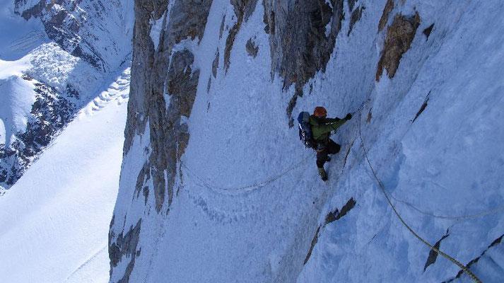 Tiefblick nach der 150 m langen Traverse in die NW-Flanke; Ralf im Aufstieg am Fixseil © Gerlinde Kaltenbrunner