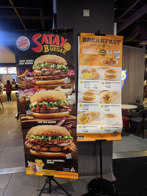 バーガーキングのサテバーガーと隣のローカルハンバーガーチェーン(?)の朝食の看板がせめぎ合う(KLIA2/Gateway)