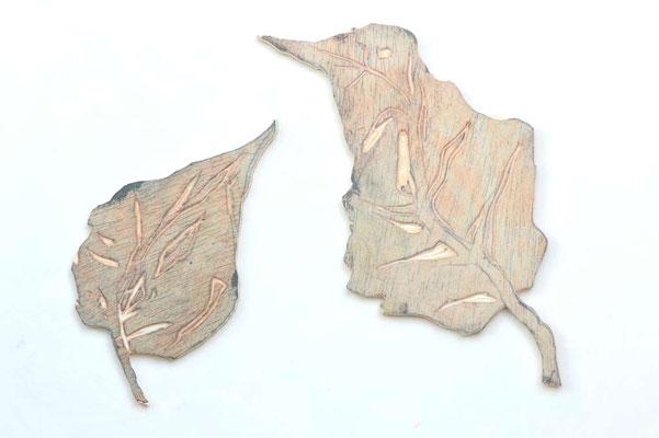 Aus einer Holzplatte ausgesägte Blätter.