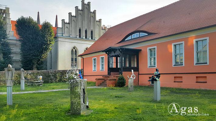 Immobilienmakler Joachimsthal - Skulpturengarten am Rathaus im Hintergrund die Schinkelkirche
