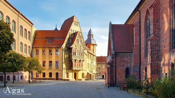 Makler Nauen - Historische Gebäude am Martin-Luther-Platz.  K.-Kollwitz-Grundschule (links), Ev. Pfarrkirche Sankt Jakobi (rechts)