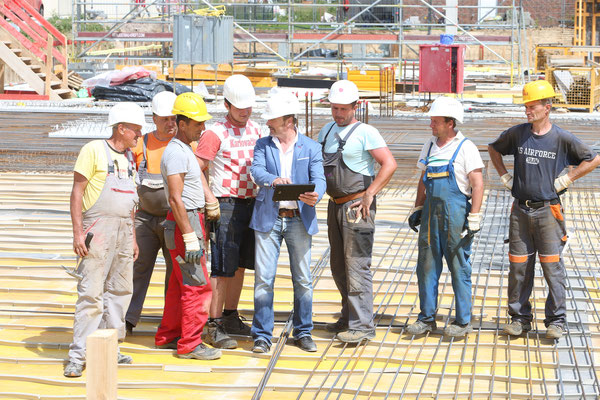 Moderator Till Demtroeder demonstriert den Bauarbeitern die Funktionsweise der Baucam