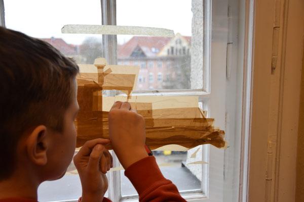 Bild wird auf der Folie am Fenster Lage für Lage geklebt