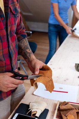 Max Muzio schneidet Leder für die Trommelschläger während dem Trommelbaukurs