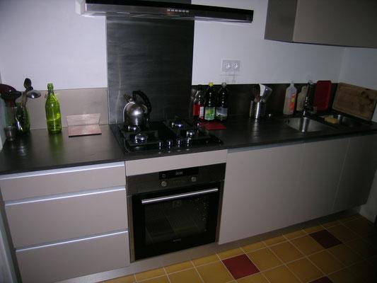 Cuisine avec plan de travail en Silestone. Finition des portes, casseroliers et tiroir en stratifié Taupe, sur mesure.